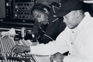Two men sitting in front of a sound mixer- Music producer management