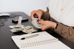 A woman counting money: Effective tips on how to get funding for your music projects.