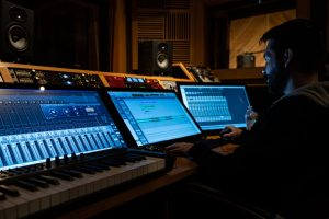 A man in music studio producing using sound mixers-What Makes A Hit Song – Secrets You Should Know