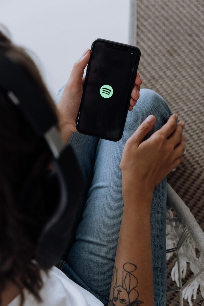 A picture of someone holding a smartphone with the Spotify logo on the screen: Spotify Canvas Feature
