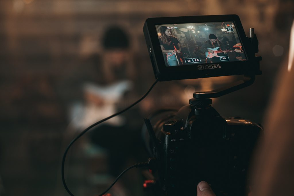 A picture of a video camera with someone playing the guitar in front of it: Music Video Concepts