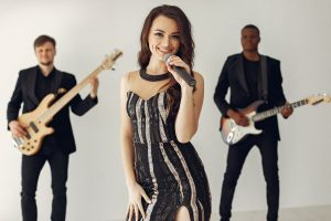 A lady wearing a black and silver dress singing with two guitarist standing behind her - How to be an independent artist
