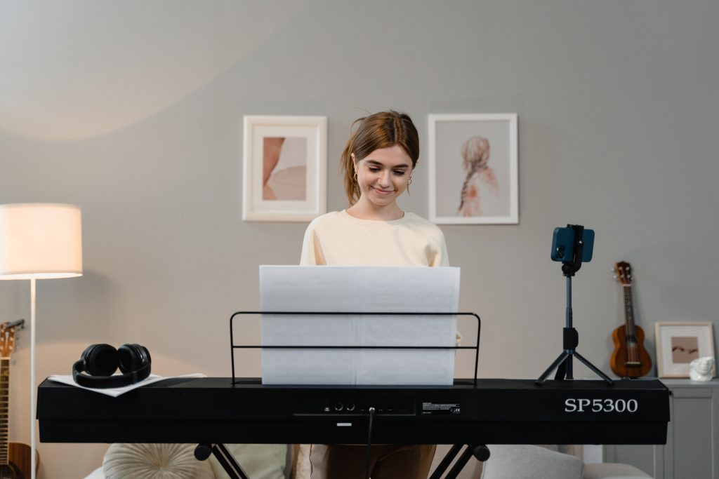 A lady wearing a white cream t-shirt smiling at a keyboard and a music manuscript- Music Producer Tips For Beginners.